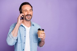 Portrait of cheerful positive man have free time relax after work day speak smartphone hold mug hot latte beverage wear stylish clothes isolated over purple color background