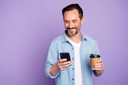 Portrait of cheerful positive man have free time relax after work use smartphone check social network hold mug with hot beverage wear denim jeans shirt isolated over violet color background