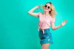Portrait of cheerful pretty caucasian girl with long blond curly hair, wearing sunglasses gesturing with arms looking at camera full of happiness isolated on blue background