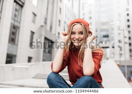 Portrait of cheerful Scandinavian woman with beautiful face and smile sitting indoors. Positive hipster wearing casual colorful clothes posing for pictures, she puts on red hat.