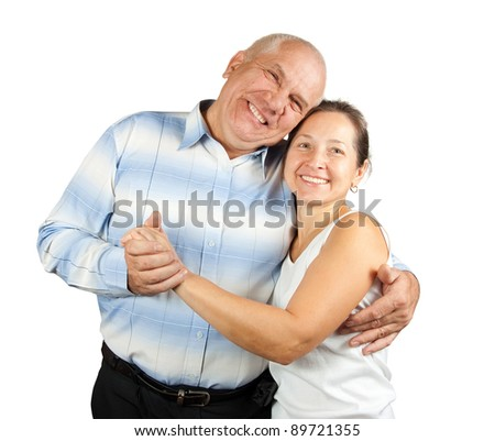 Portrait of cheerful senior couple embracing over plain background