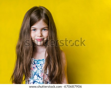 Stock Photo Portrait of cheerful smiling little cute little girl on yellow background isolated