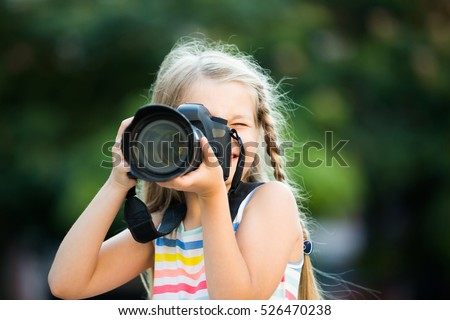 Portrait of cheerful smiling little girl making photo with big camera in hands outdoors