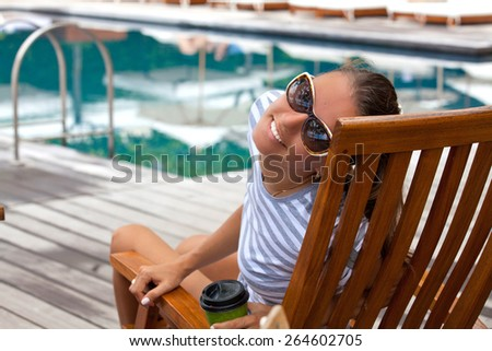 Portrait of cheerful woman, relaxing at the luxury poolside. Girl at travel spa resort pool. Summer luxury vacation. (focus on woman face)
