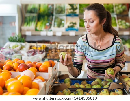 Portrait of cheerful woman selecting fruits at store
