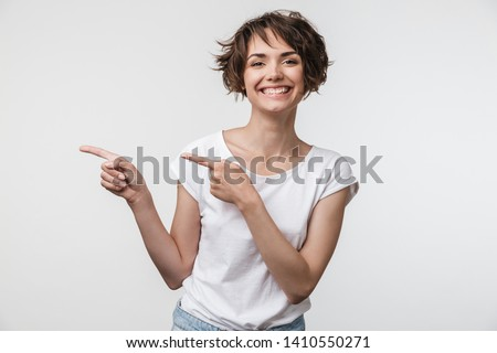 Portrait of cheerful woman with short brown hair in basic t-shirt rejoicing and pointing fingers at copyspace isolated over white background