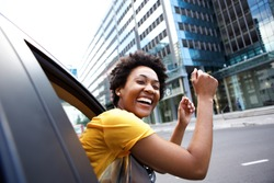 Portrait of cheerful young african woman looking out the car window with her arms raised