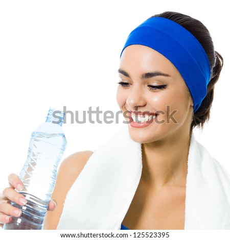 Portrait of cheerful young attractive woman in fitness wear drinking water, isolated over white background