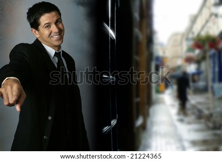 Portrait of cheerful young businessman pointing