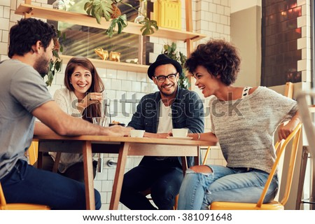 Portrait of cheerful young friends having fun while talking in a cafe. Group of young people meeting in a cafe. Stock photo ©