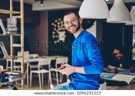 Portrait of cheerful young man in casual wear smiling at camera while updating software on modern touch pad device using wireless 4G internet.Positive hipster guy installing app on tablet in office