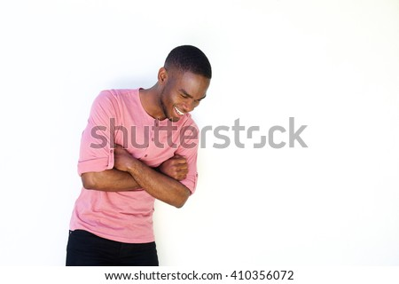Portrait of cheerful young man standing against white background and looking down #410356072