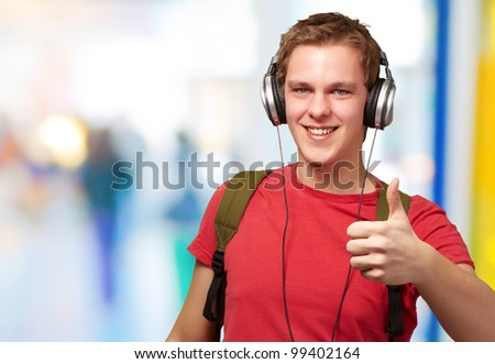 portrait of cheerful young student listening music and gesturing good with headphones indoor