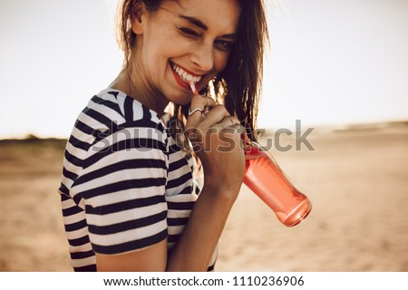 Portrait of cheerful young woman drinking beverage with straw from glass bottle. Girl drinking a soda outdoors on a summer day. Stock foto ©