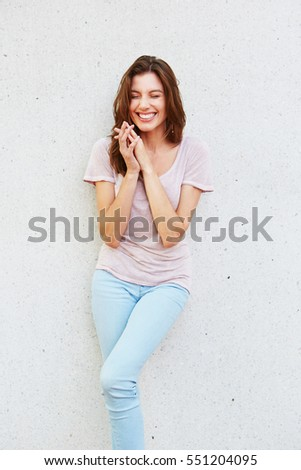 Portrait of cheerful young woman smiling against white wall #551204095