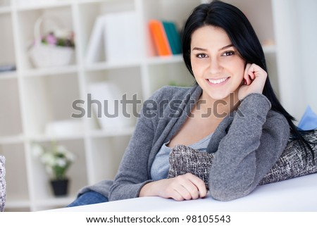 Portrait of cheerful young woman smiling while relaxing on couch