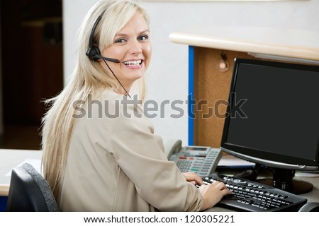 Portrait of cheerful young woman using computer at reception desk