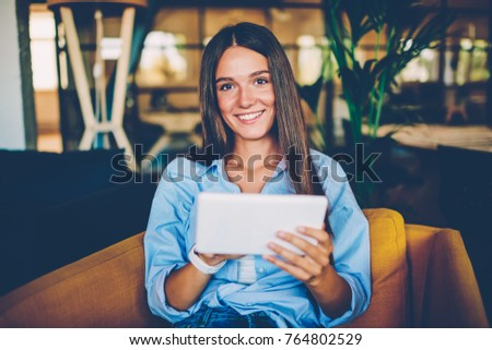 Portrait of cheerful young woman using portable pc for blogging in social networks sitting in coffee shop,happy hipster girl looking at camera while downloading new application from networks on tablet