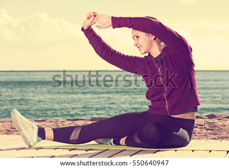 Shutterstock Portrait of cheerful young woman working out at seaside