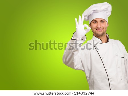 Portrait Of Chef Showing Ok Sign On Green Background
