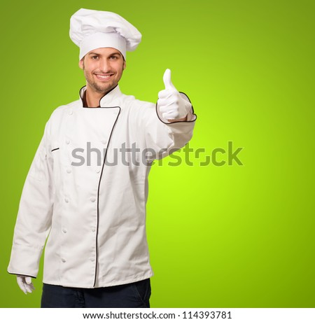 Portrait Of Chef Showing Thumb Up Sign On Green Background