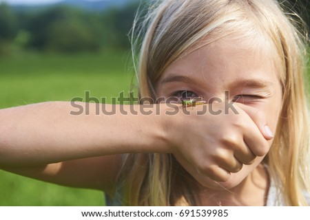 Portrait of Child blond girl with cricket insect sitting on her hand on summer meadow. Children who are not afraid of insects. Focused to cricket