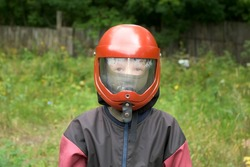 Portrait of child boy in costume and helmet to flying in aerodynamic tube. Entertainment in the fresh air, flying in aerodynamic tube. Outdoors activity.
