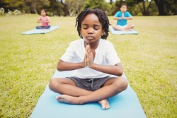 Portrait of child doing yoga with friends in the park