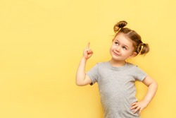 Portrait of child girl with finger pointed up. Little kid in pose has idea isolated on yellow blackboard. Success, bright idea, creative ideas and innovation technology concept