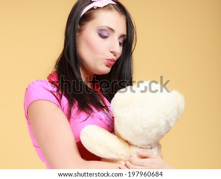 Portrait of childish young woman with headband holding toy. Infantile girl in pink hugging kissing teddy bear on orange. Longing for childhood. Studio shot.