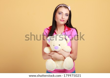 Portrait of childish young woman with headband holding toy. Infantile girl in pink hugging teddy bear on orange. Longing for childhood. Studio shot.