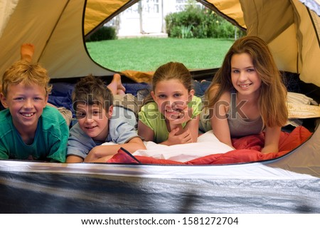 Portrait of children camping lying inside tent in garden at home