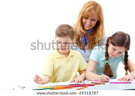 Portrait of children drawing pictures and teacher standing near