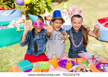 Portrait of children gesturing while sitting at table in yard during party #702265678