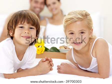 Portrait of children in bed with their parents after having breakfast