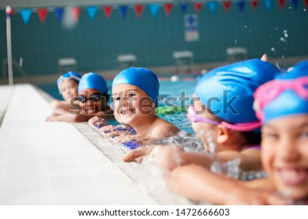 Portrait Of Children In Water At Edge Of Pool Waiting For Swimming Lesson Foto stock ©
