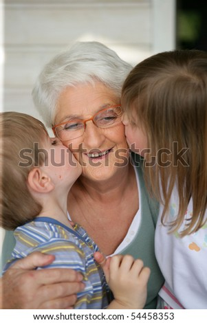 Portrait of children kissing a senior woman on the cheek