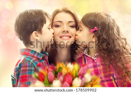 Portrait of children kissing her mother with flowers. Mother`s day concept. Family holiday
