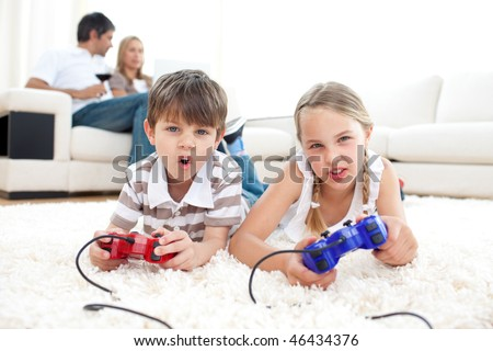Portrait of children playing video games lying on the floor