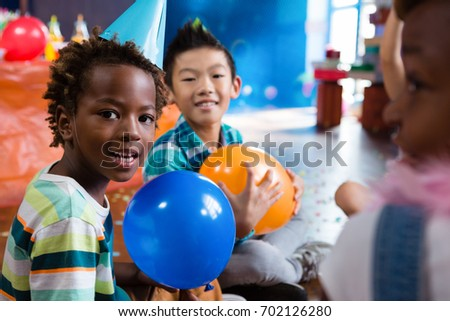Portrait of children playing with balloon in rood during party