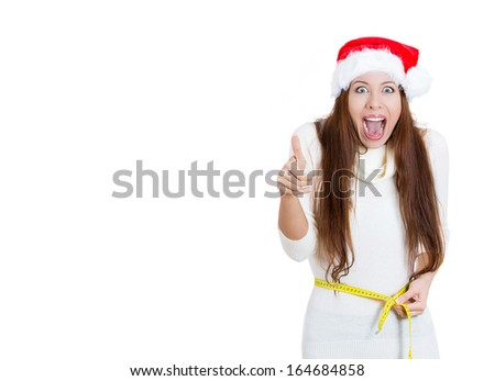 Portrait of Christmas fitness woman excited about weight loss measuring waist with tape wearing santa hat screaming excited showing thumb up, isolated on white background. Positive emotion, expression
