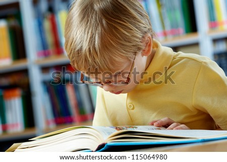 Portrait of clever boy reading book in library