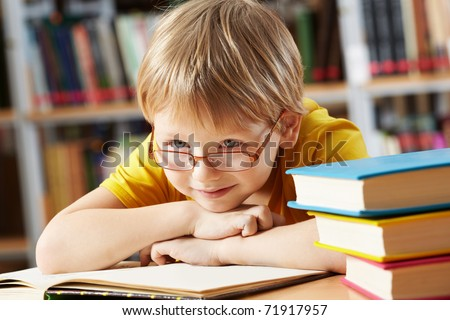 Portrait of clever boy with open book in library