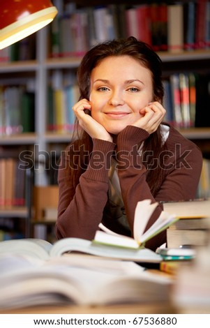 Portrait of clever student looking at camera and smiling in college library