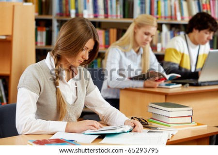 Portrait of clever students preparing lessons in college library