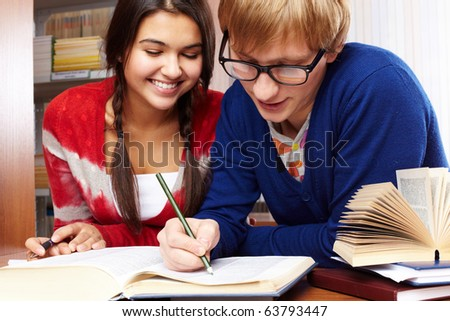 Portrait of clever students preparing lessons together in college library