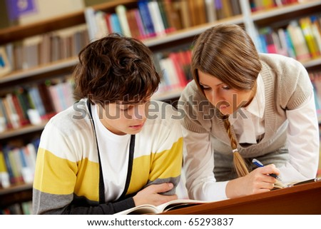 Portrait of clever students reading book in college library