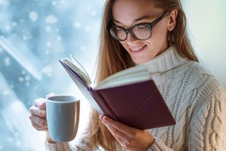 Portrait of comforting happy cozy woman in glasses in knitted winter white warm sweater drinks a cup of hot cocoa during reading favorite book on a window sill by the window at home in winter time.
