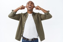 Portrait of complaining annoyed african-american man, shouting at neihbours upstairs, complaining people listening music too loud, having noisy party, shut ears from discomfort, cant work home