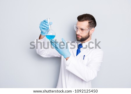 Portrait of concentrated busy scientist with stubble in white lab coat, gloves examine, looking at  flask with multi-colored liquid in his arm, isolated on grey background